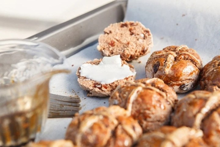 A tray of freshly baked vegan hot cross buns cut in half and slathered with coconut butter