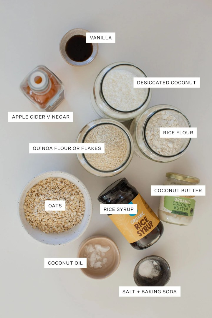 Overhead shot of a plate of Healthy ANZAC Biscuits with one cookies half eaten, and a hot drink