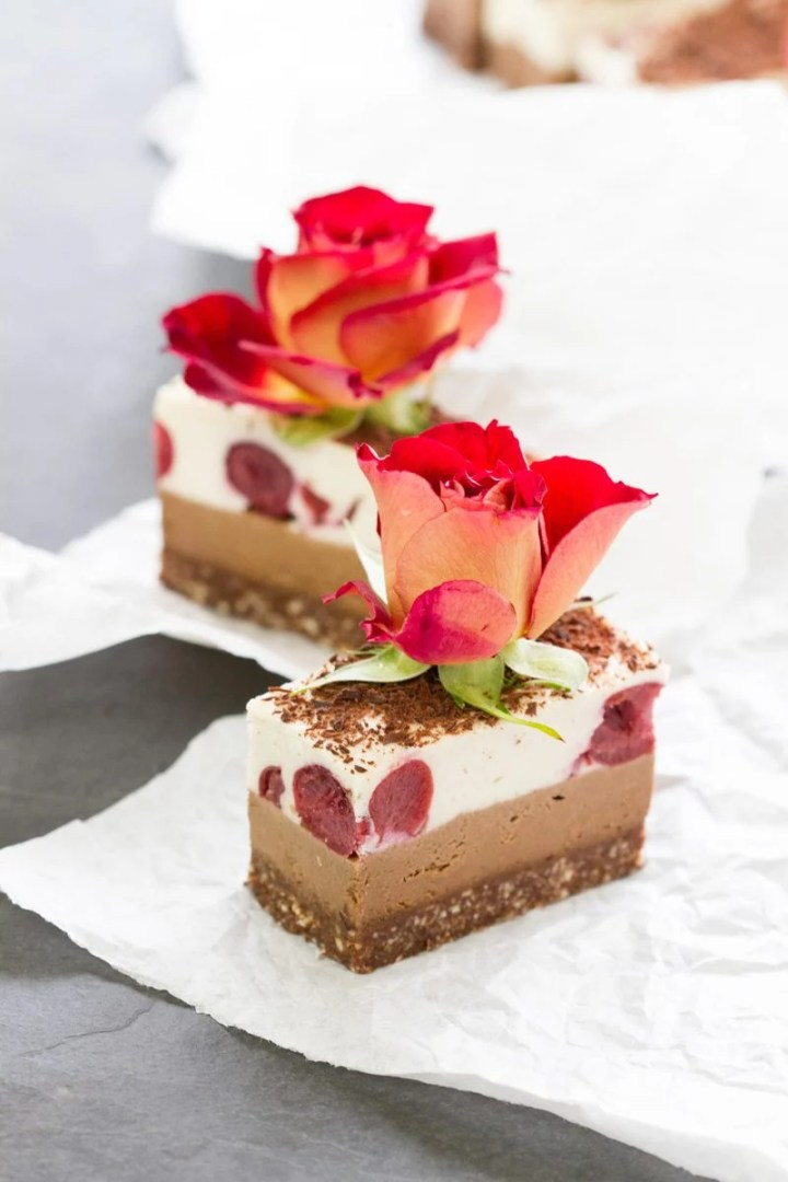 Two Raw Black Forest Slices with roses on top, profile view of the layers