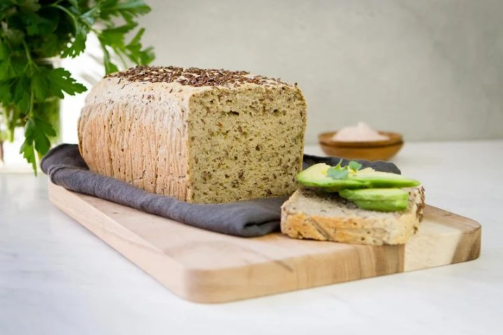 Freshly baked and sliced loaf of Millet Bread on a wooden board