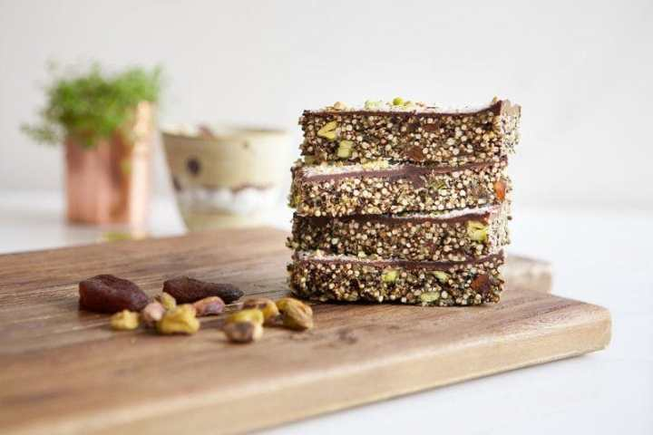Apricot Chocolate Popped Quinoa Bars stacked on a wooden board