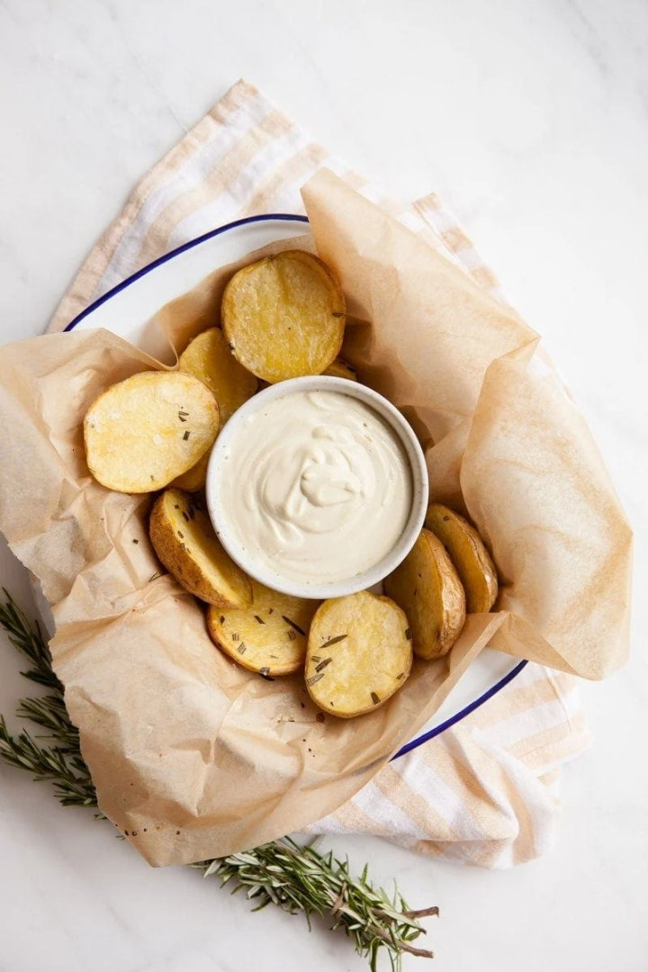 A tray full of roasted potatoes with a dish full of creamy vegan aioli in the centre