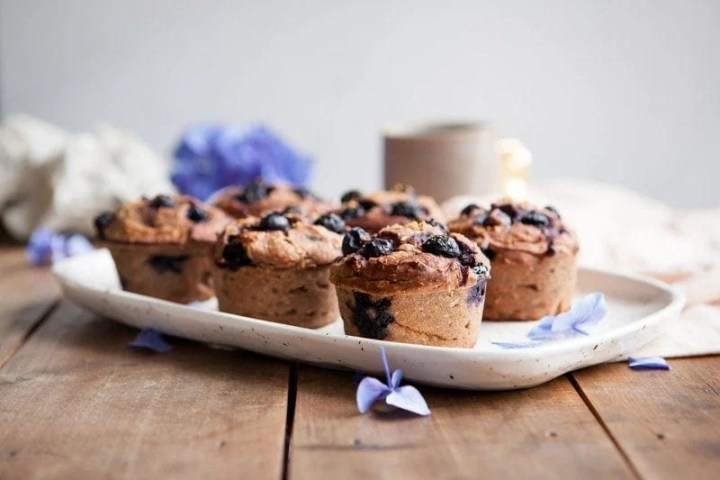 A tray of Gluten Free Blueberry Muffins made with teff flour on a rustic table