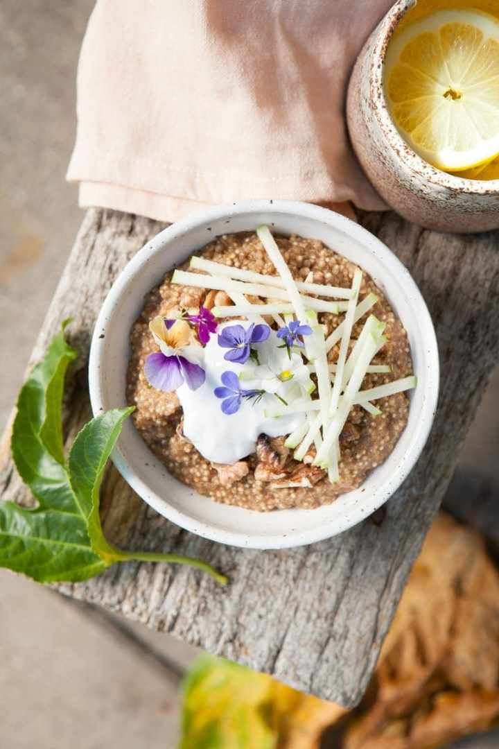 Close up of Quinoa Porridge with coconut, apple and fresh flowers on top