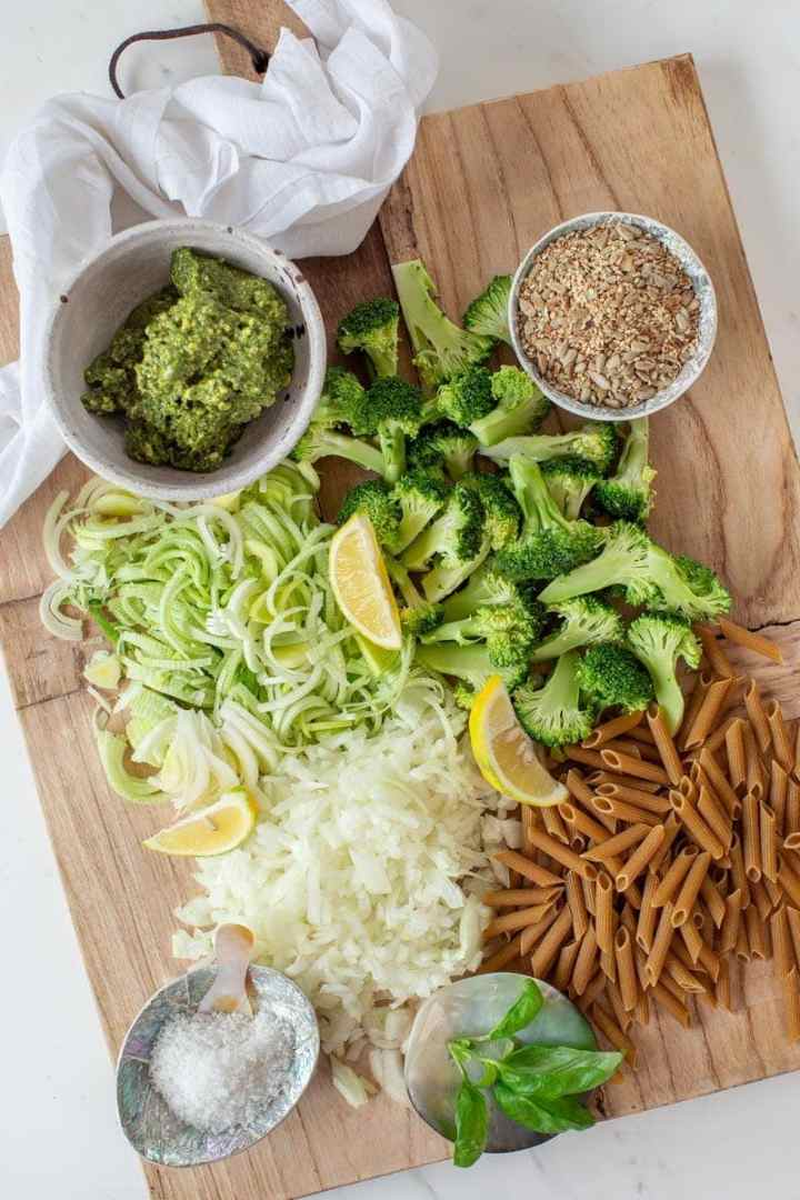 All ingredients for making broccoli pasta laid out on a wooden board