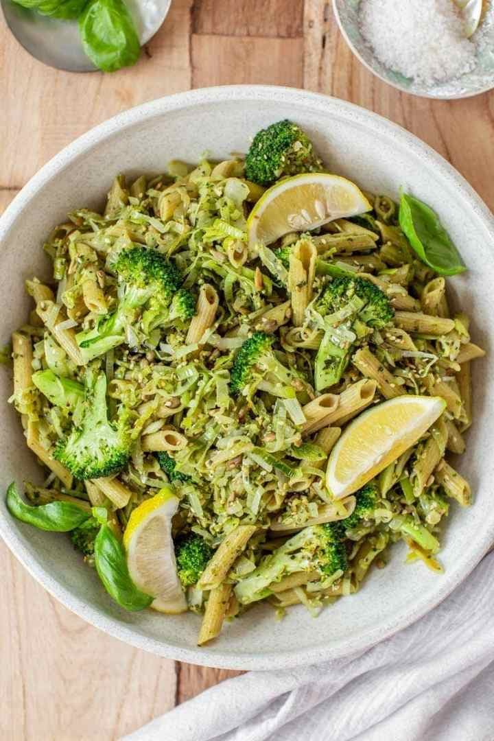 Overhead shot of a large bowl of broccoli pasta tossed with fresh pesto, with lemon wedges on top