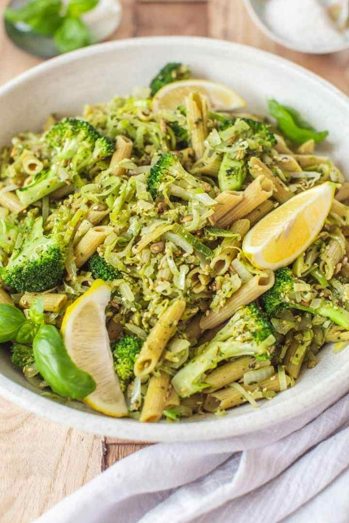 Serving bowl filled with broccoli pasta and fresh basil leaves
