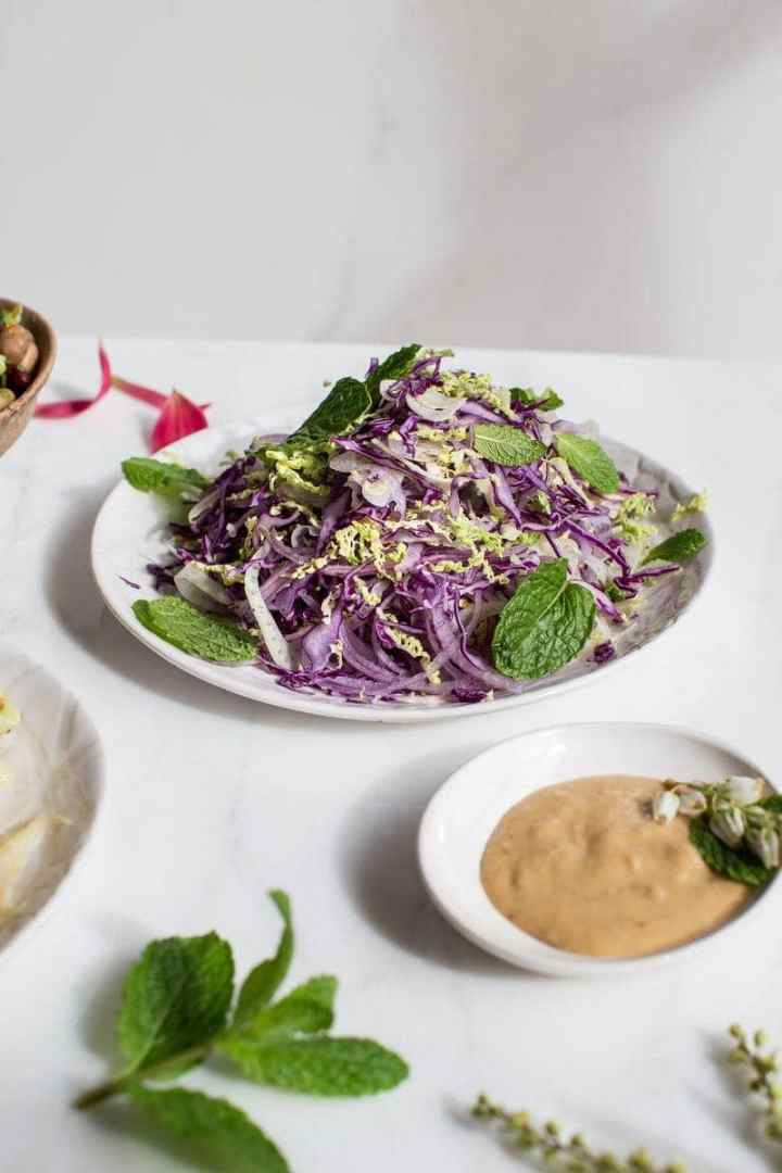 Dinner table with a heaped serving plate of fresh slaw and creamy miso tahini dressing ready to serve