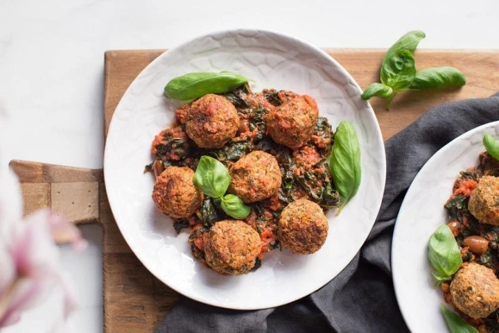 A plate of vegan lentil meatballs in sauce on a chopping board