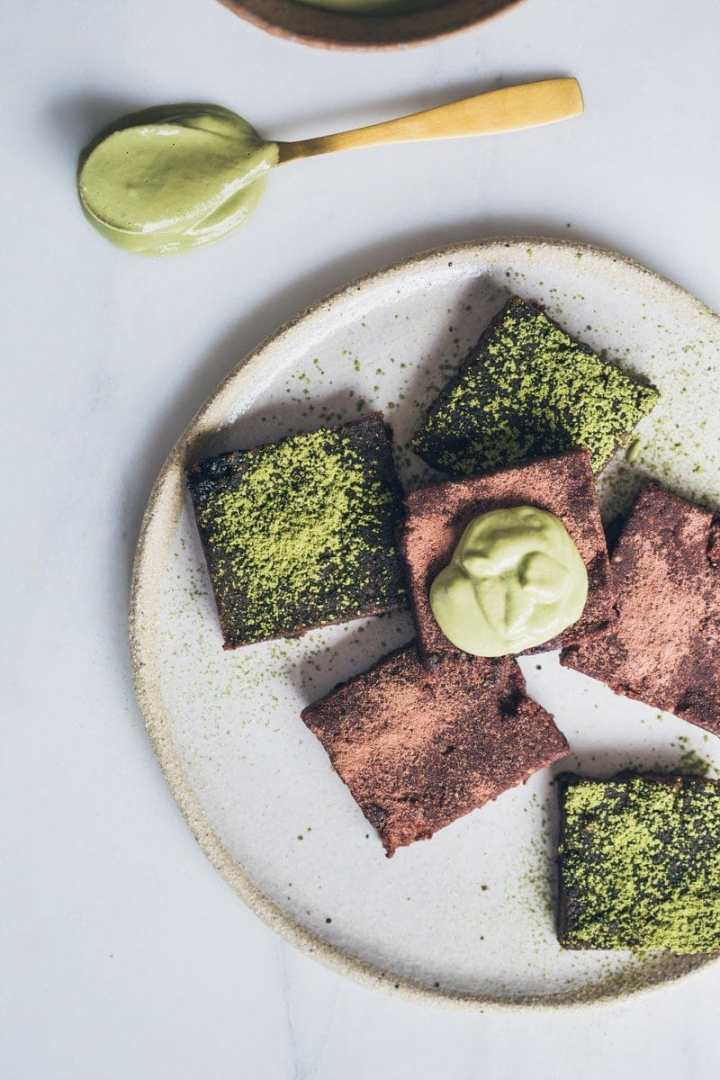 Close up of raw vegan brownies on a ceramic plate with a dollop of matcha cream