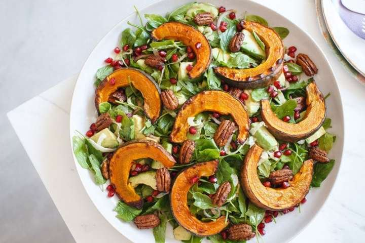 Squash salad next to a stack of coloured ceramic plates