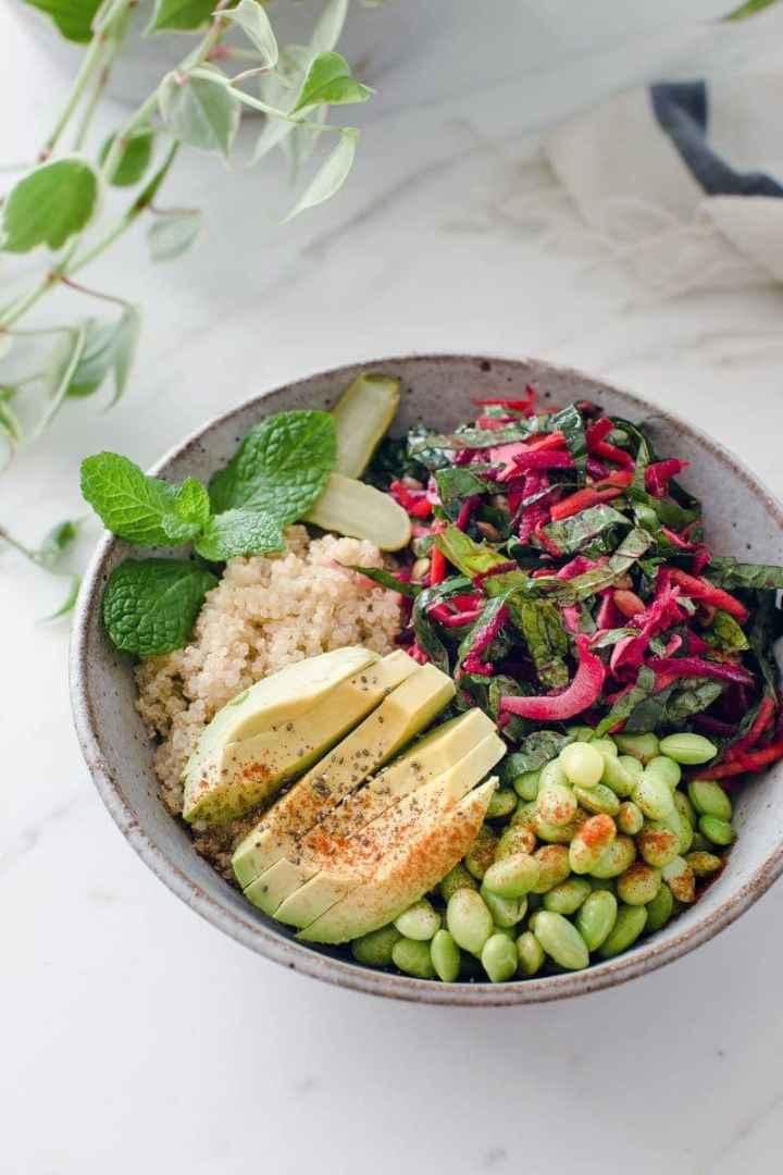 A Buddha bowl containing fresh raw beetroot salad, quinoa, edamame beans and avocado