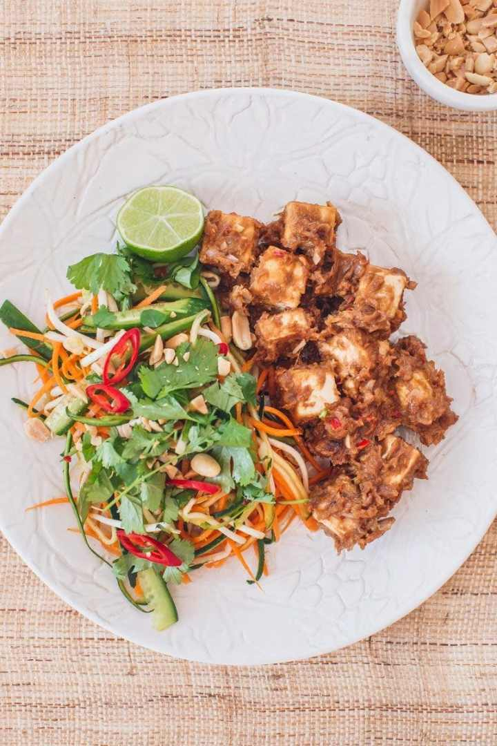 Close up of a plate filled with tofu satay and fresh vegetables on a woven placemat