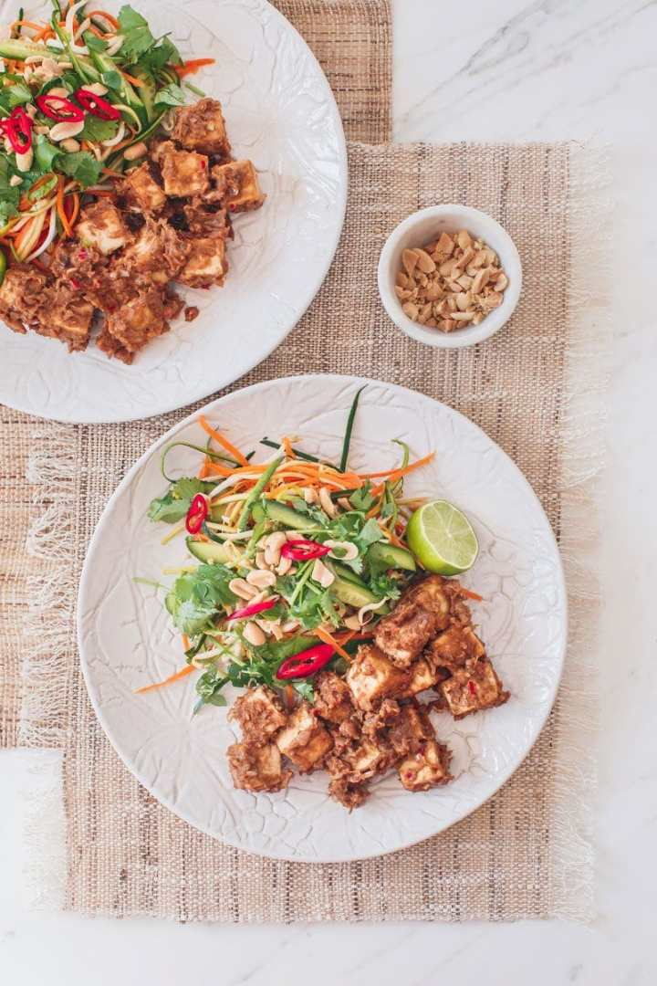 Two dinner plates filled with fresh raw vegetable salad and tofu in a thick satay sauce on the kitchen table