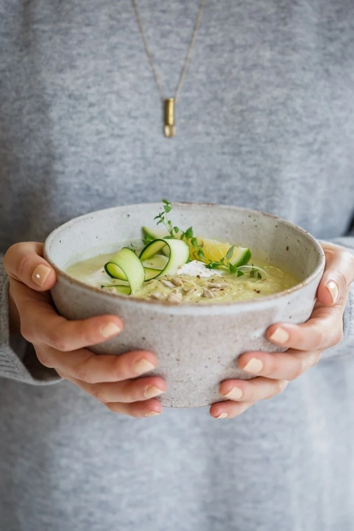 Lauren in a cozy grey sweater holding a ceramic bowl of homemade celeriac soup with beautiful garnishes
