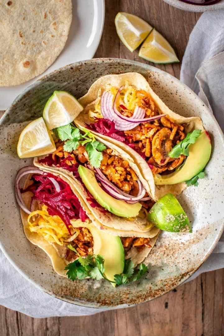 Close up of vegan tacos filled with tempeh mince and fresh vegetables