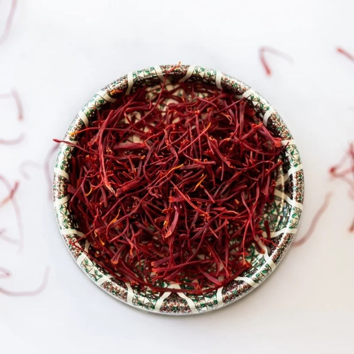 Close up of a tiny dish filled with bright red dried saffron stamens