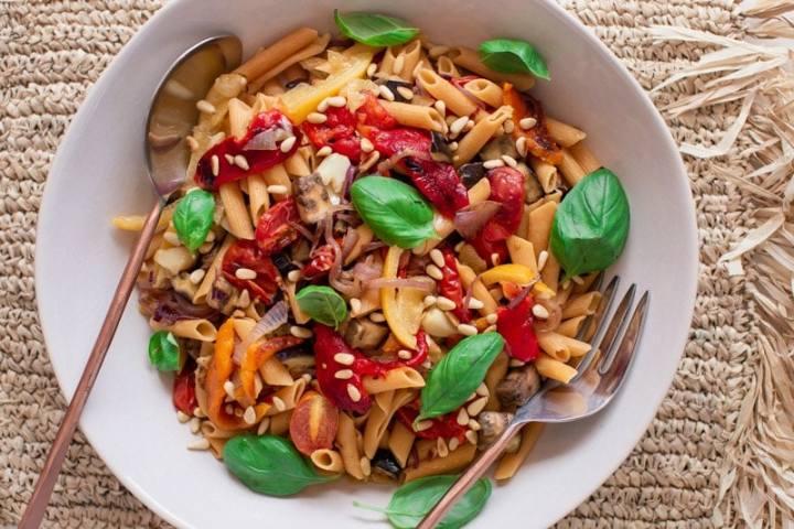 Close up of a bowl of Italian vegan pasta salad with salad servers
