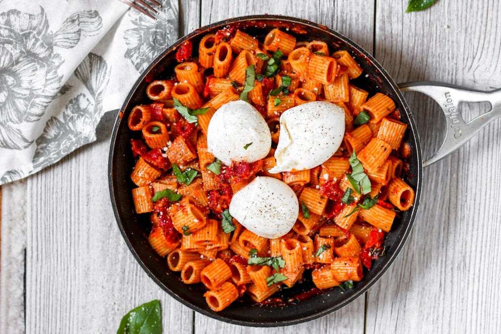 overhead shot of the pasta in a pan topped with 3 balls of Burrata.