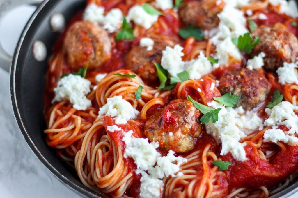 Angled shot of spaghetti noodles swirled with meatballs, fresh mozzarella, and parsley.