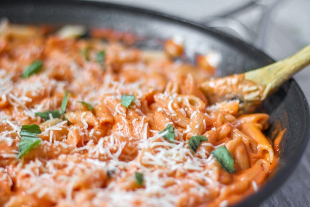 penne vodka in a pan with a wood spoon.