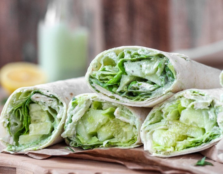 Cucumber Wraps with Green Goddess Dressing on a wood surface.