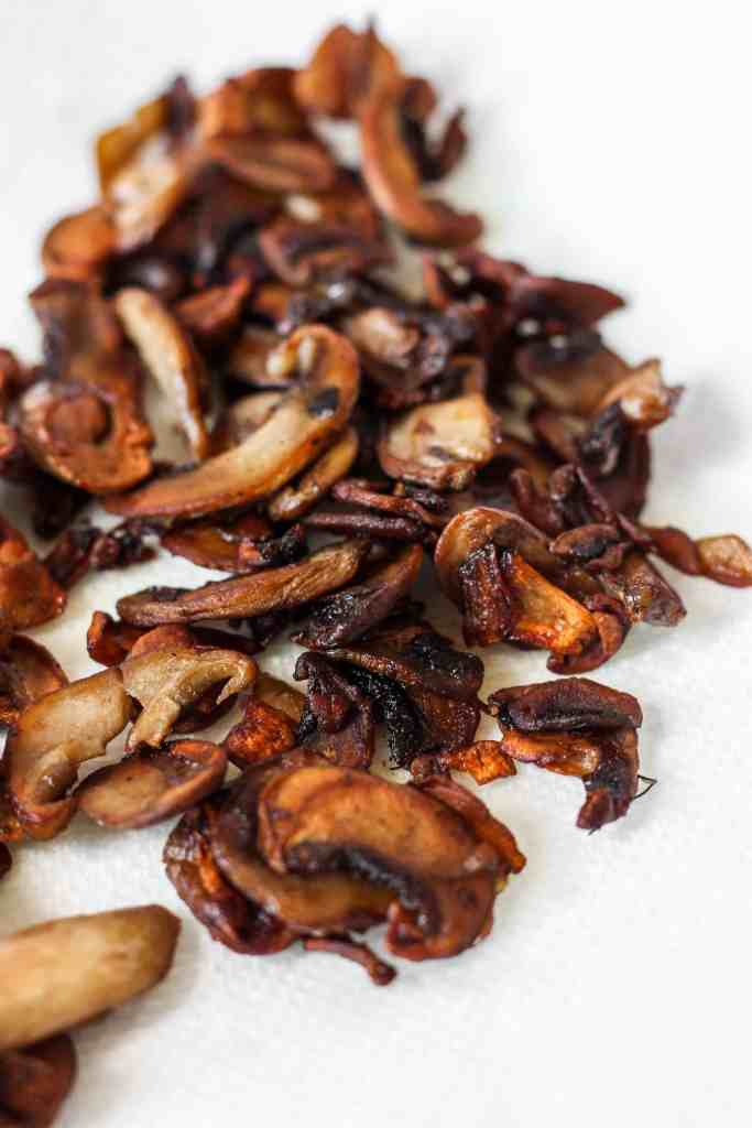 sauteed thin slices of mushrooms on a paper towel