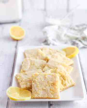 A white rectangular plate with lemon sugar cookies squares.