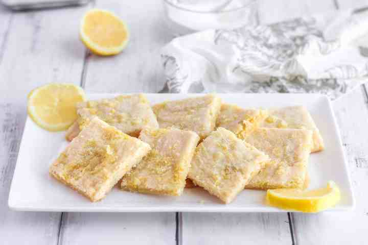 a white rectangular plate with lemon sugar cookie squares and slices of lemons. In the background a white floral napkin and a slice of lemon.