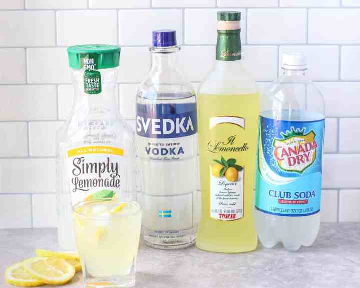 The ingredients for the cocktail displayed on a grey cement surface in front of a white subway tile background. From left to right the ingredients as displayed as a bottle of Simply Lemonade, a bottle of Svedka vodka, a bottle of limoncello, and a bottle of club soda. In the foreground a glass of the cocktail and several lemon slices.