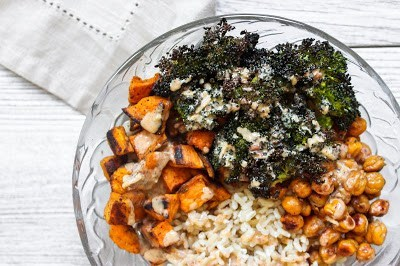 Overhead shot of a glass bowl with roasted sweet potatoes, roasted broccoli, crispy chickpeas, and rice covered in a tahini dressing.