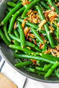 Grean beans with almonds and lemon zest in a silver pan.