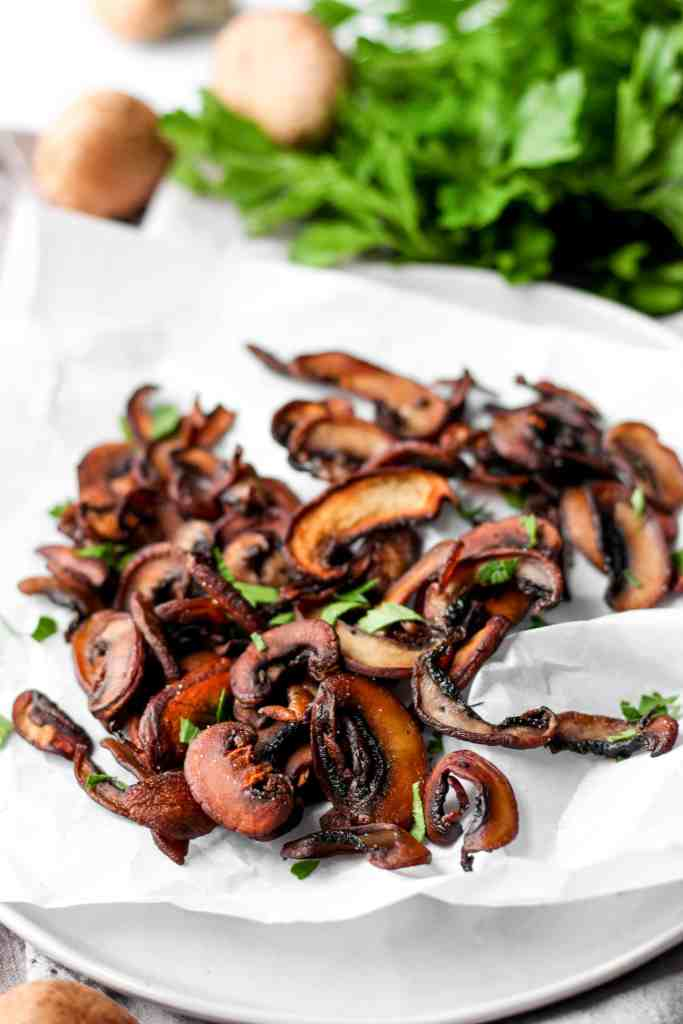 mushroom chips on a white plate with parsley.