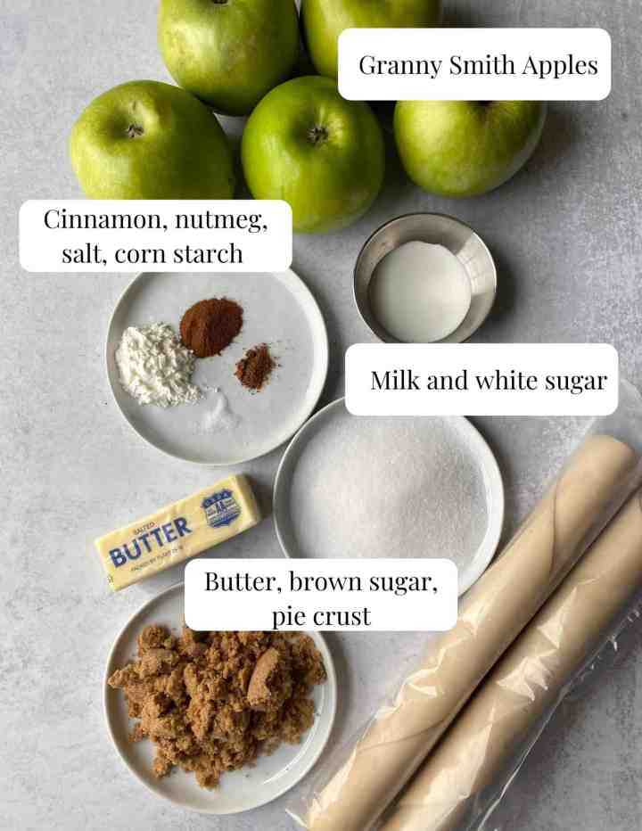 image of the ingredients, butter, brown and white sugar, salt, corn starch, spices, dough, apples, and milk.