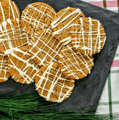 overhead shot of a plate of gingersnaps drizzled with white chocolate.
