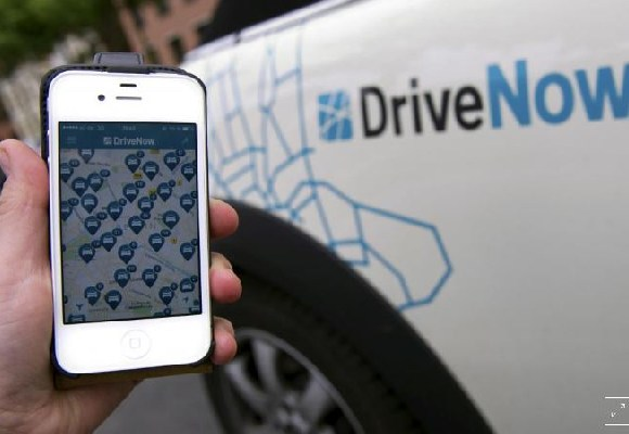 A smartphone displaying the DriveNow app with cars available in Berlin's city centre