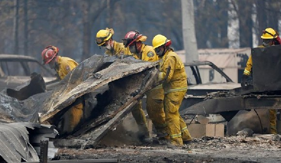 California Fire firefighters comb through a house destroyed by the Camp Fire in Paradise, USA