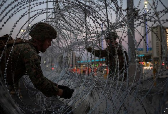 Some military men fixing a wire gauze around the border
