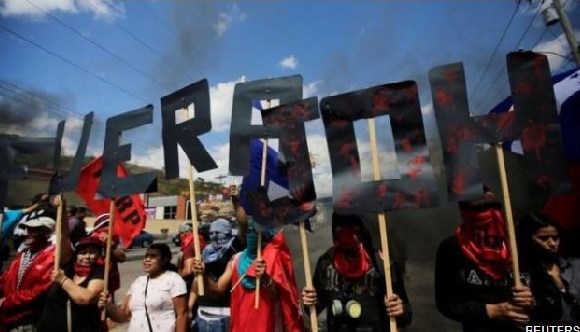 Demonstrators form the words 'JOH (Juan Orlando Hernández) Out' in Tegucigalpa