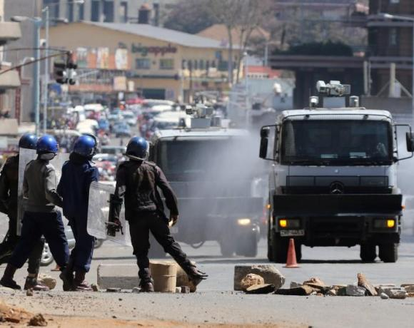 Anti riot police clear roads during a protest by opposition youths who were demonstrating against alleged brutality by security agents in the capital Harare, Zimbabwe