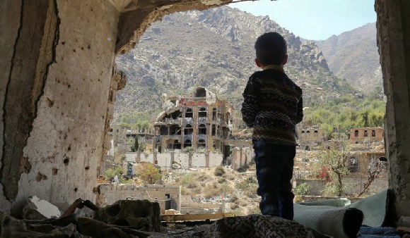 Yemeni child looking out at buildings that were damaged in an air strike in the southern Yemeni