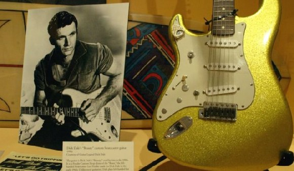 An early photo of Dick Dale alongside a custom Fender guitar at an exhibit in California