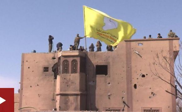 Kurdish TV showed the SDF raising a yellow flag on top of buildings seized from IS in Baghuz