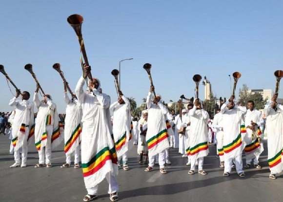 Men blow traditional trumpets during the 123rd anniversary celebration of the battle of Adwa