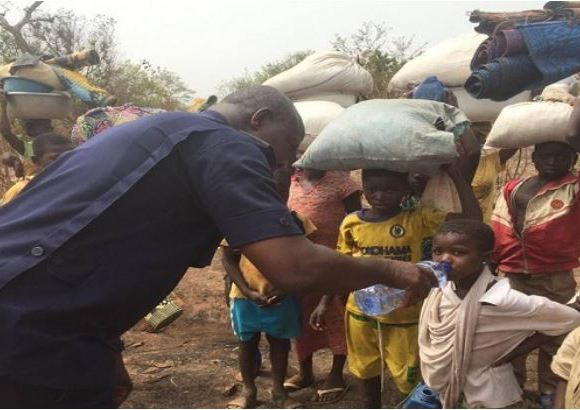 The commander offering water to the displaced children