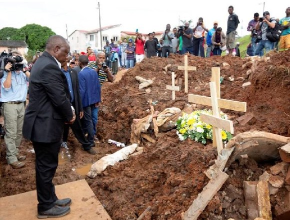 President Cyril Ramaphosa lays a wreath at a debris of a house destroyed after massive flooding