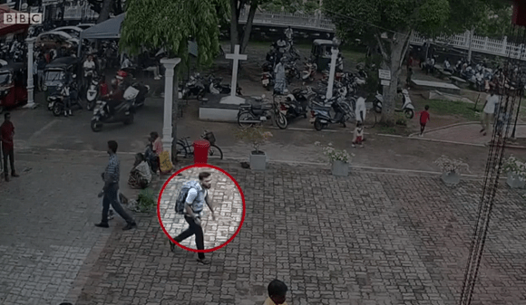 The footage shows a man wearing a large backpack calmly walking towards St Sebastian's church