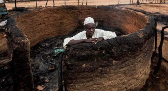 A man is seen inside a burnt house during clashes between nomads and residents in Deleij village