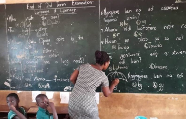 Teacher writes on Chalkboard