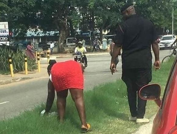 The woman being led by police to clean a stretch of the Kejetia road